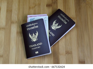 Thai passports with banknote on table.