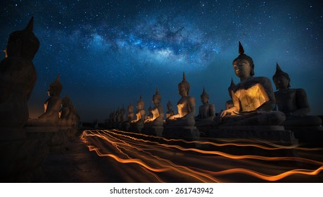 Thai people in Candly festival with Buddha statue and milky way in dark night sky in Thailand