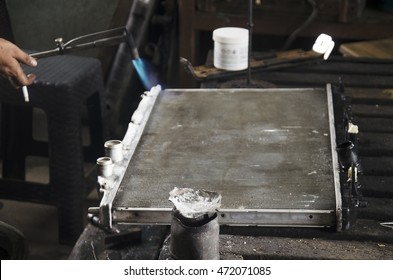 Thai people use lead and gas welding for fix and solder radiator of car at local garage at Nonthaburi, Thailand