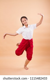 Thai performance art, woman dancer student dancing in traditional red loincloth; studio portrait of woman dancer in asian Thai traditional elegant dance move; young adult asian woman dancer model