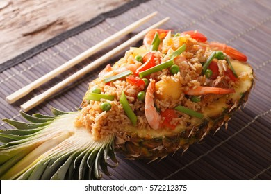 Thai pineapple stuffed with rice, shrimp, chicken and vegetables closeup on the table. horizontal