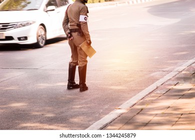 Thai police : Traffic police stand in the middle of the road and hold a logbook to warn traffic violators on city streets.