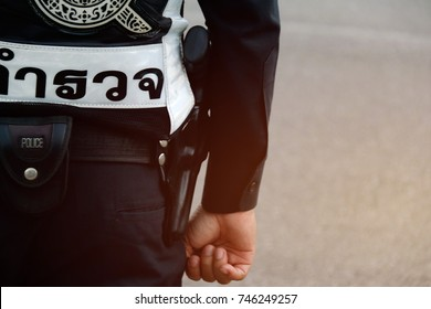 Thai police:Dressing and carrying firearms of Thai police :Close up police carrying a gun, waistband, and wearing a suit with a Thai-language logo:Guardian Thai Language  translate into English police