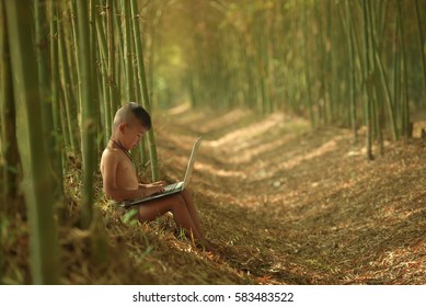 Thai poor children sitting computer tablet on the outdoor lily