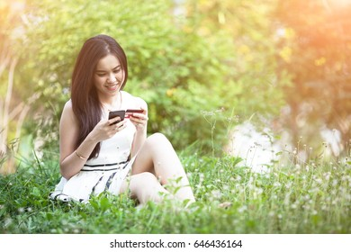 Thai pretty woman using mobile for shopping online with credit card at the park