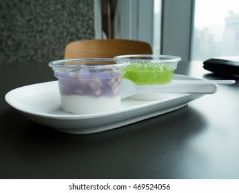 Thai pudding with coconut topping in plastic cup