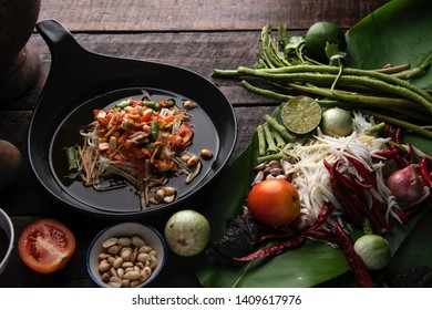 Thai recipe. Papaya salad (Som Tam) dished, ingredient on the wooden table with wooden mortar. Thai food concept. Top view.