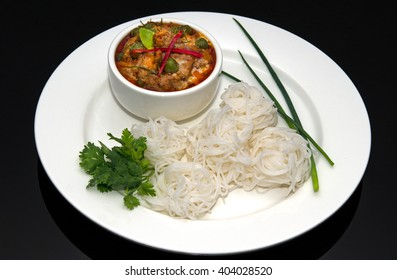 Thai Red Beef curry, white rice noodles on black background