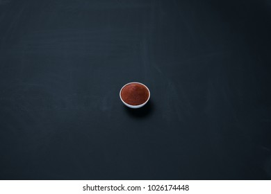 Thai red curry paste in a small bowl isolated on blackboard background.