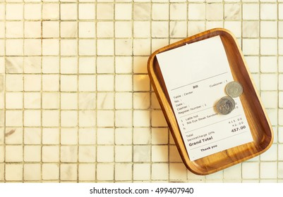 Thai restaurant bill payment receipt on white marble tile table top