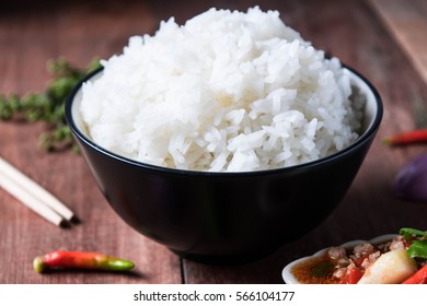 Thai rice in a cup placed on a black wooden floor.