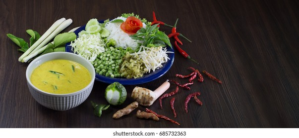 Thai rice noodle eaten with curry and veg. thai food (Thai language Kanom jeen) on blue dish and green bowl, All on brown wooden background / Selective focus and adjustment for cover, banner, header