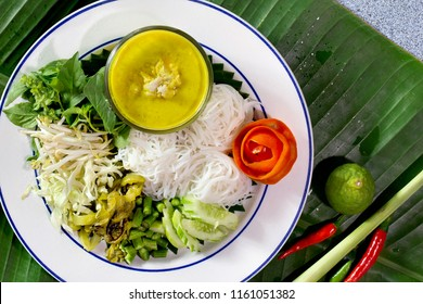 Thai rice noodle eaten with spicy curry crab and veg. thai food (Thai language Kanom jeen) on white dish and curry in bowl All on banana leaf background / Select focus and top view