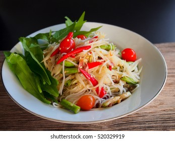 Thai rice noodle papaya salad with pickled fish sauce on wooden table