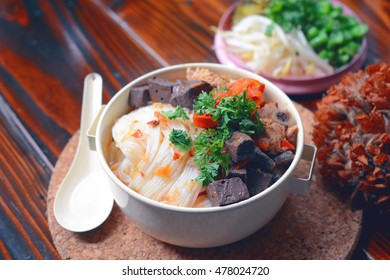 """thai rice vermicelli with spicy pork sauce. traditional northern thai rice noodle with pork in tomato soup and fresh vegetable called """"ka-nom jeen nam ngiew"""" in thai"""