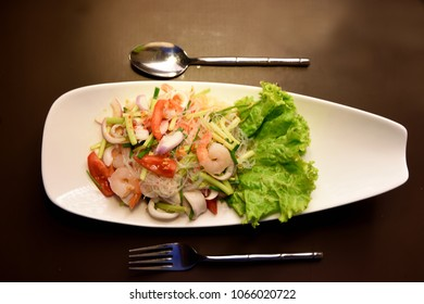 Thai Salad food mixed with prawn,tomato, onion and lots of other vegitables photographed against dark wooden background