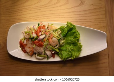 Thai Salad food mixed with prawn,tomato, onion and lots of other vegitables photographed against wooden background