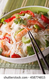 Thai salad with glass noodles, prawns and peanuts in a bowl close-up. vertical