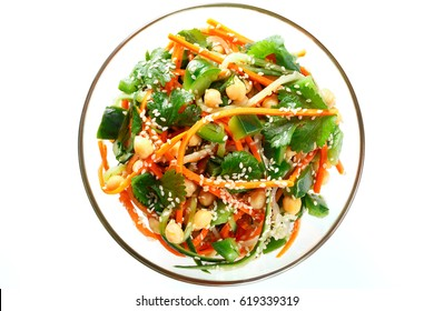Thai salad from noodles raw carrots and cucumber with chickpeas, cilantro and sesame in sweet and sour sauce. Concept of healthy diet, cleansing the body, losing weight. Isolated on white, top view.