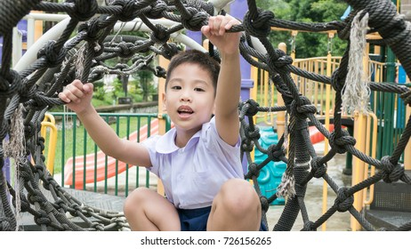 Thai school boy in uniform play alone at the rope net in the play ground.