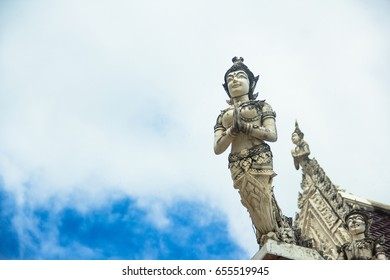 Thai sculpture figure of a deva on the roof of buddhist church, in the temple, Thailand