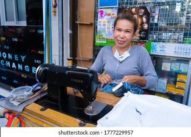 Thai seamstress woman in street clothing fast repair shop. Bangkok / Tailand - 02.04.2020