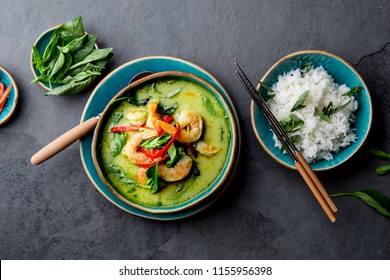 THAI SHRIMPS GREEN CURRY. Thailand tradition green curry soup with shrimps prawns and coconut milk. Green Curry in blue plate on gray background