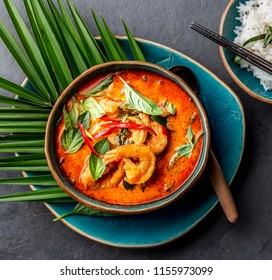 THAI SHRIMPS RED CURRY. Thailand tradition red curry soup with shrimps prawns and coconut milk. Panaeng Curry in blue plate on gray background.