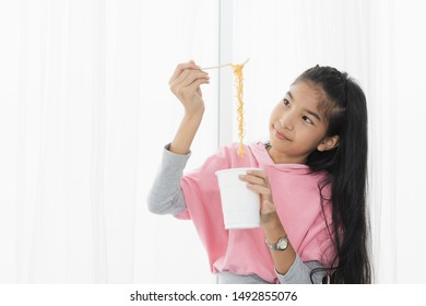 thai sian girl eating instant noodles at the white window