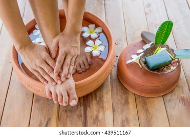 Thai spa, foot spa with wash by both hand in earthenware dish with white flower, stone body scrub, leaf and green soap  on wooden background