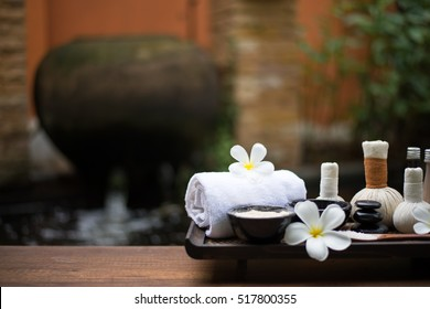 Thai Spa massage compress balls, herbal ball on the brown wooden with treatments spa for wellness and healthy ,background nature, Thailand.  Healthy Concept.