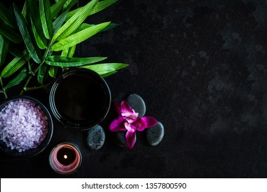 Thai Spa.  Top view of hot stones setting for massage treatment and relax with purple orchid on blackboard with copy space.  Green leaf with black stones pile for spa therapy.  Lifestyle and Healthy