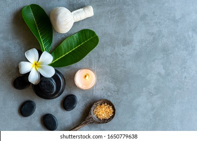 Thai Spa. Top view of white Plumeria flower setting for massage treatment and relax on black blackboard for text banner and copy space. Spa flower with black stones pile for body therapy Lifestyle