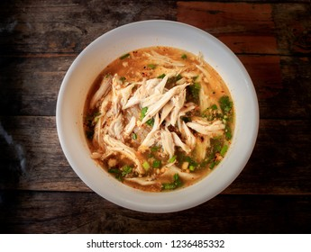Thai spicy chicken noodle soup on wood table, top view