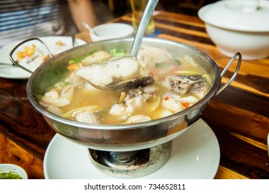 Thai spicy freshwater fish soup with herbs, served in big bowl. Tom Yam Pla. Thai famous street local food. recommended menu for tourist and traveler. image for background, wallpaper and menu list.