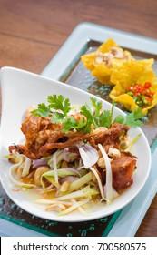 Thai spicy salad with deep fried soft shell crab and sliced green mango, Yum Pu Nim in Thai cuisine
