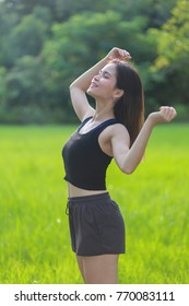Thai sport girl relaxing and exercising in the nature in sportwear as health and energy concept