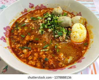 Thai street food Spicy Tomyum noodle soup with pork balls, Boiled Eggs. Asian spicy seafood noodle soup. Close up of Thai Tom Yum spicy lime with pork, egg. Noodles Tom yum.