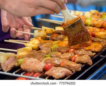 Thai street vendor sells pork satay - bbq fried pork meat on sticks.