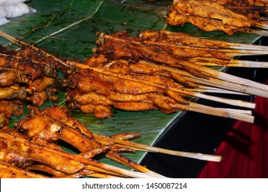 Thai street vendor style marinated grilled chicken wings or Thai barbecue onto bamboo skewer.