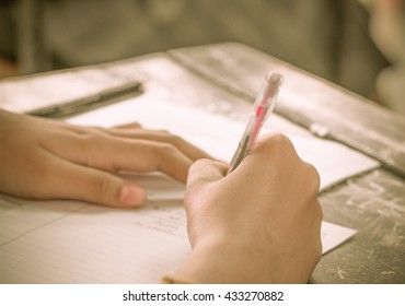 Thai student writing a test in exercise on exams sheet, selective focus