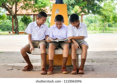 thai students sit on concrete bunch and read a book together