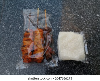 Thai style barbeque chicken on sticks with sticky rice in plastic bag. Street food in Bangkok.