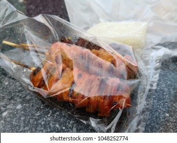 Thai style barbeque chicken on sticks with sticky rice in plastic bag. Street food in Bangkok