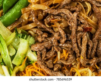 Thai Style Beef Noodles in Chilli Sauce Against a Dark Oak Wood Background