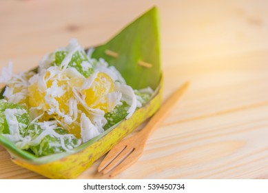 Thai style cassava dessert in banana leaf plate on wood table .