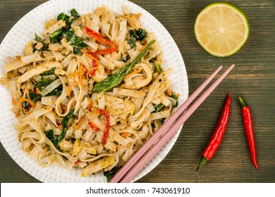 Thai Style Chicken Pad Thai With Noodles On A Green Wooden Background
