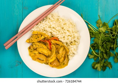 Thai Style Chicken Panang Curry With Jasmine Rice Against a Blue Wooden Background With a bunch of Corriander Herbs and Chop Sticks