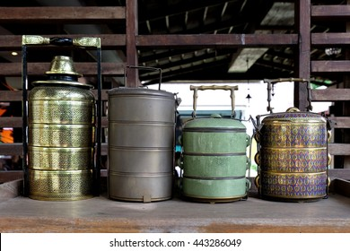 Thai style food carriers, a stack of cylindrical vessels, strung one above another by metalstrips which also form a handle