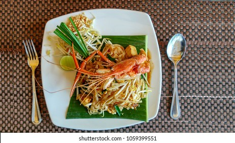 Thai style food with lobster on white plate and photographed against mat